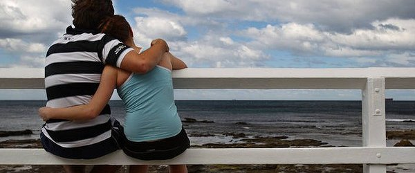 A boyfriend and girlfriend hugging and looking at the ocean